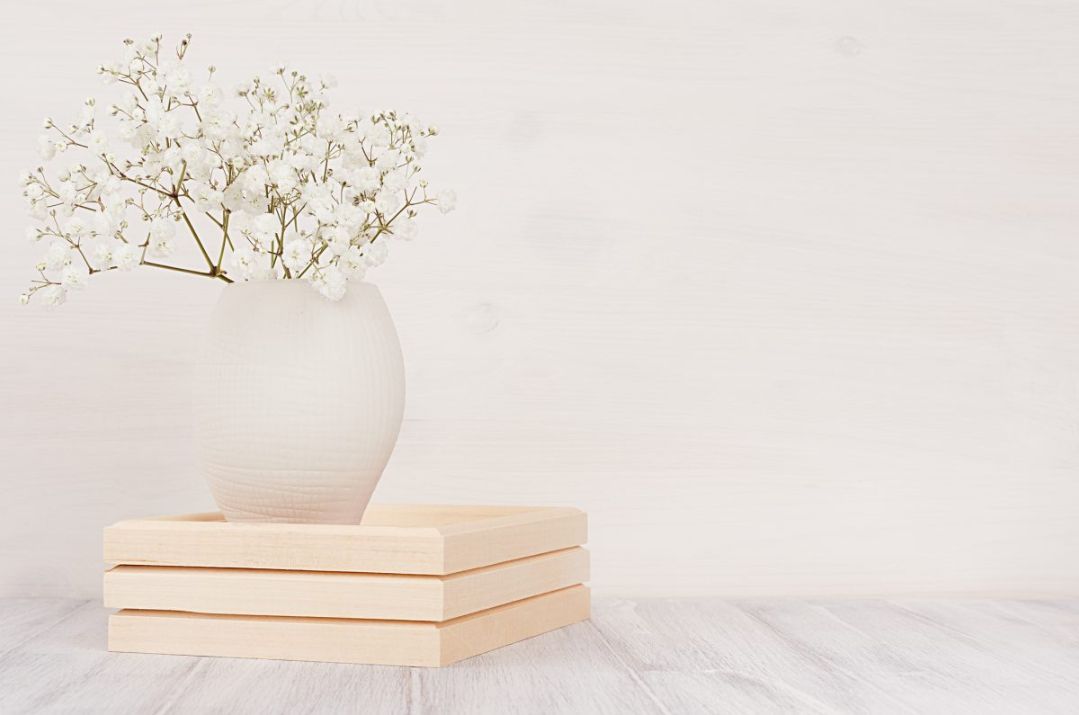 Soft home decor of white small flowers in ceramic vase on white wood background. Interior.